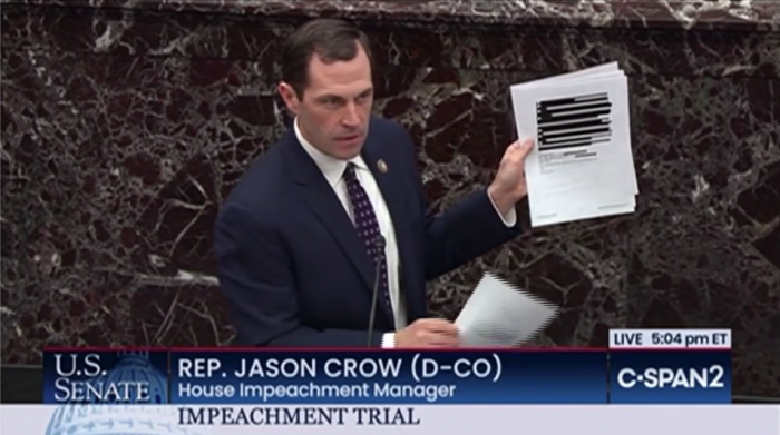Representative Jason Crow holds up a heavily-redacted email from the Office of Management and Budget during the Senate impeachment trial on Wednesday